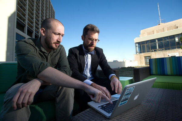 Two engineers on a roof deck in front of a keyboard. One bites his lip in concentration with hands on the keyboard while the other points at the laptop's screen
